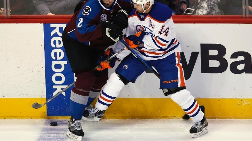 Colorado Avalanche defenseman Nick Holden, left, and Edmonton Oilers right wing Jordan Eberle work for the puck along the boards during the first period of an NHL hockey game Saturday, Dec. 19, 2015, in Denver. (AP Photo/David Zalubowski)