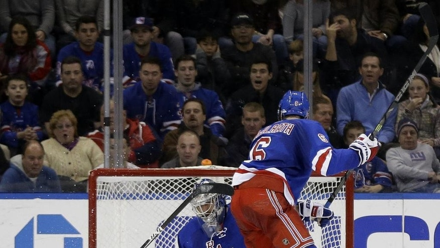Washington Capitals' T.J. Oshie, left, hits the ice as he scores a goal past New York Rangers goalie Henrik Lundqvist, center, as Dylan McIlrath (6) looks on during the second period of the NHL hockey game, Sunday, Dec. 20, 2015, in New York. (AP Photo/Seth Wenig)