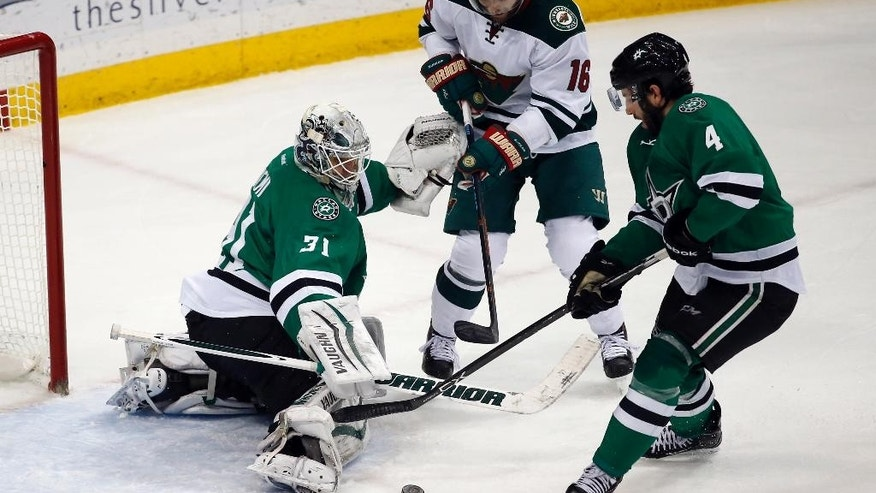Dallas Stars goalie Antti Niemi (31), from Finland, blocks a shot by Minnesota Wild left wing Jason Zucker (16) as Stars defenseman Jason Demers (4) reaches for the puck, in the third period of an NHL hockey game, Monday, Dec. 21, 2015, in St. Paul, Minn. The Stars won 6-3. (AP Photo/Ann Heisenfelt)