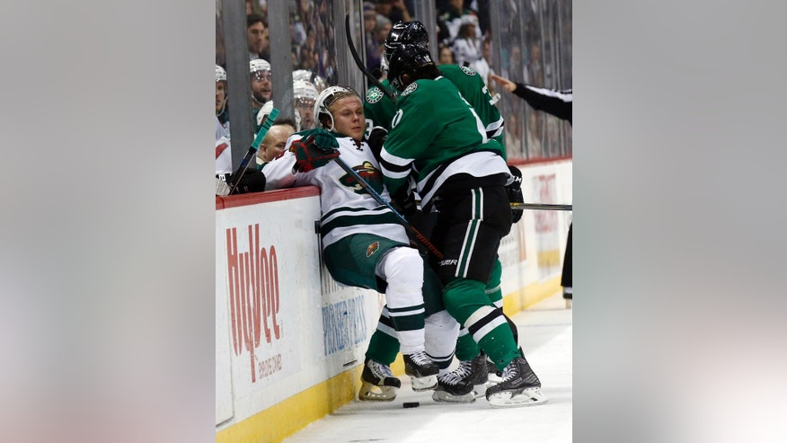 Minnesota Wild center Mikael Granlund, left, from Finland, is knocked into the boards by Dallas Stars left wing Patrick Sharp, right, in the second period of an NHL hockey game, Monday, Dec. 21, 2015, in St. Paul, Minn. (AP Photo/Ann Heisenfelt)
