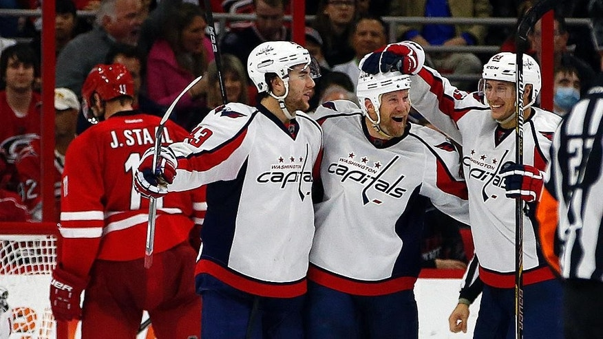 Washington Capitals' Jason Chimera (25) is congratulated on his goal by teammates Tom Wilson (43) and Jay Beagle, right, during the second period of an NHL hockey game against the Carolina Hurricanes, Monday, Dec. 21, 2015, in Raleigh, N.C. Washington won 2-1. (AP Photo/Karl B DeBlaker)