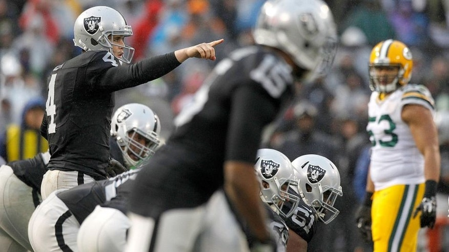 Dec 20, 2015; Oakland, CA, USA; Oakland Raiders quarterback Derek Carr (4) calls a play against the Green Bay Packers in the fourth quarter at O.co Coliseum. The Packers defeated the Raiders 30-20. Mandatory Credit: Cary Edmondson-USA TODAY Sports