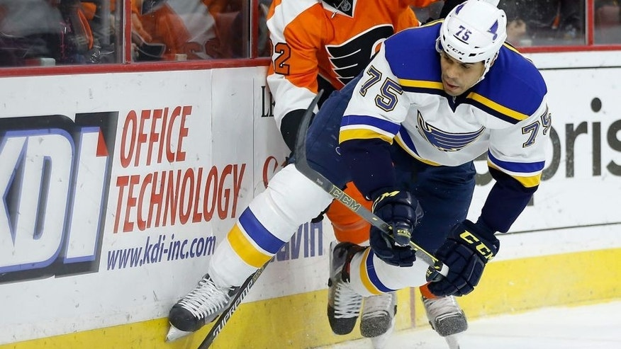 St. Louis Blues' Ryan Reaves (75) and Philadelphia Flyers' Luke Schenn (22) chase after a loose puck during the first period of an NHL hockey game, Monday, Dec. 21, 2015, in Philadelphia. (AP Photo/Matt Slocum)