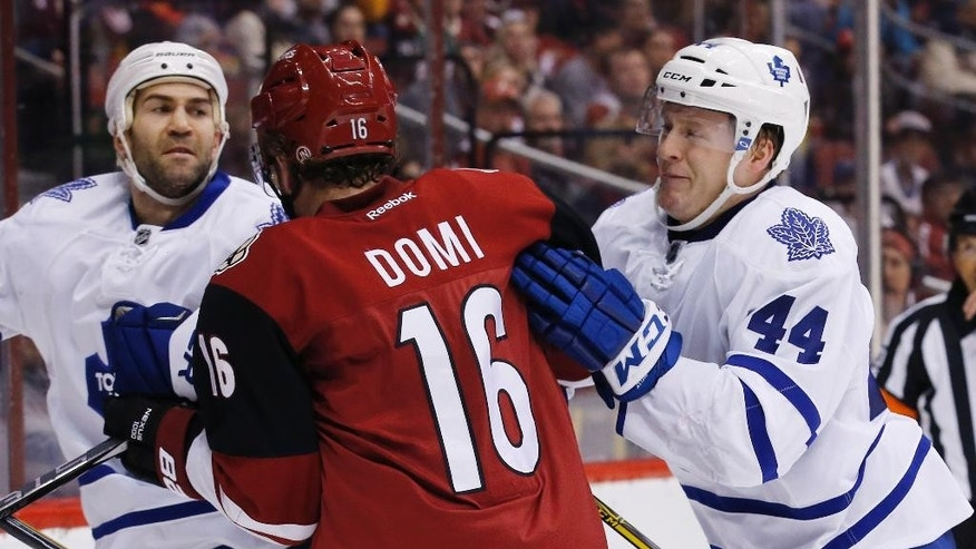 Arizona Coyotes' Max Domi (16) battles Toronto Maple Leafs' Morgan Rielly (44) and Daniel Winnik, left, during the first period of an NHL hockey game Tuesday, Dec. 22, 2015, in Glendale, Ariz. (AP Photo/Ross D. Franklin)