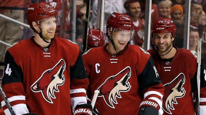 Arizona Coyotes' Shane Doan, center, celebrates his second goal against the Toronto Maple Leafs during the first period of an NHL hockey game with teammates Klas Dahlbeck, left, of Sweden, and Kyle Chipchura, right, Tuesday, Dec. 22, 2015, in Glendale, Ariz. (AP Photo/Ross D. Franklin)