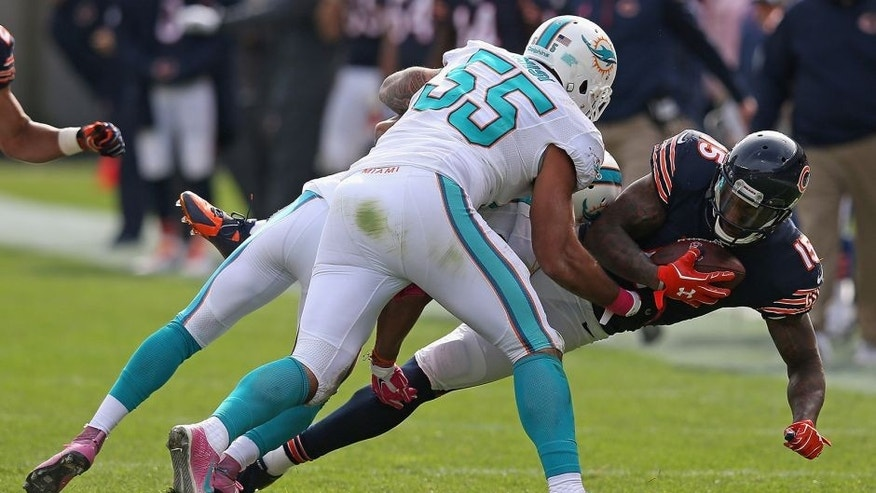 CHICAGO, IL - OCTOBER 19: Brandon Marshall #15 of the Chicago Bears is tackled by Cortland Finnegan #24 and Koa Misi #55 of the Miami Dolphins during the third quarter at Soldier Field on October 19, 2014 in Chicago, Illinois. (Photo by Jonathan Daniel/Getty Images)