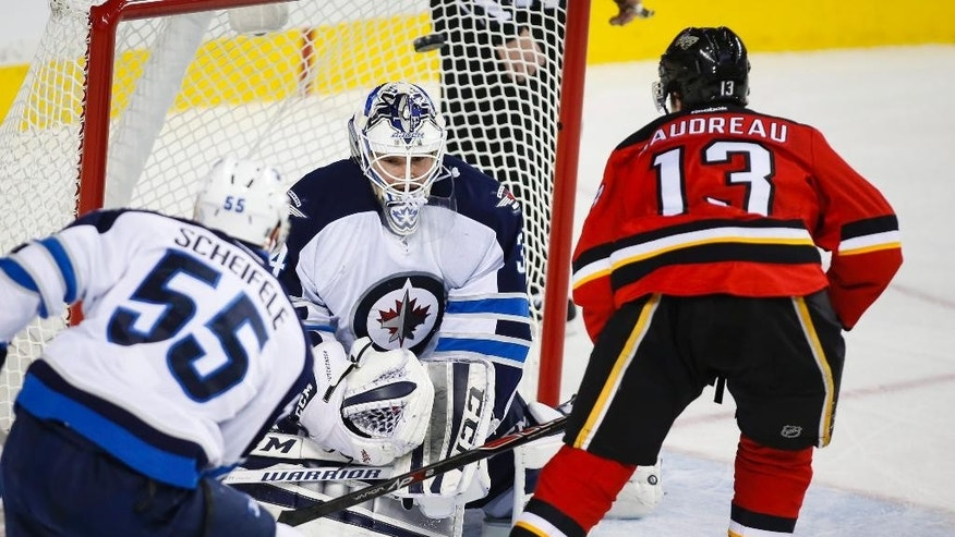 Winnipeg Jets goalie Michael Hutchinson, center, lets in a hat trick goal from Calgary Flames' Johnny Gaudreau, right, during the third period of an NHL hockey game in Calgary, Alberta, Tuesday, Dec. 22, 2015. (Jeff McIntosh/The Canadian Press via AP) MANDATORY CREDIT