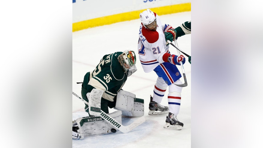 Montreal Canadiens' Devante Smith-Pelly, right, looks down to see Minnesota Wild goalie Darcy Kuemper stop a shot in the first period of an NHL hockey game, Tuesday, Dec. 22, 2015, in St. Paul, Minn. (AP Photo/Jim Mone)
