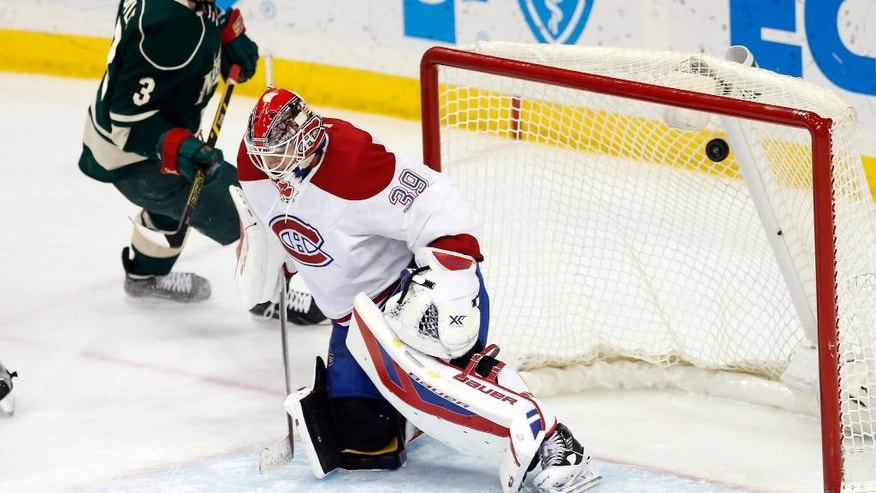 Montreal Canadiens goalie Mike Condon gives up a goal by Minnesota Wild's Charlie Coyle, left, in the third period of an NHL hockey game, Tuesday, Dec. 22, 2015, in St. Paul, Minn. The Wild won 2-1. (AP Photo/Jim Mone)