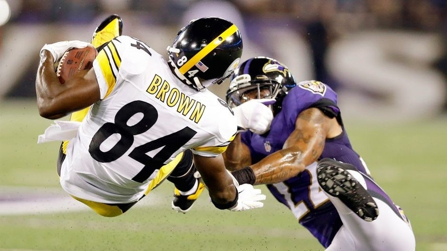 Pittsburgh Steelers wide receiver Antonio Brown (84) is tackled by Baltimore Ravens cornerback Jimmy Smith (22) during the first half of an NFL football game Thursday, Sept. 11, 2014, in Baltimore. (AP Photo/Patrick Semansky)