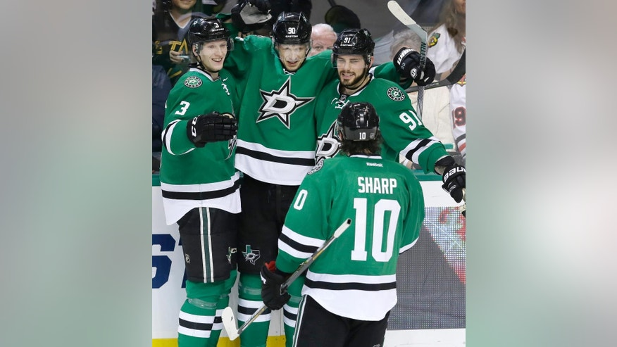 Dallas Stars center Jason Spezza (90) celebrates scoring a goal with teammates John Klingberg (3), Tyler Seguin (91) and Patrick Sharp (10) during the second period of an NHL hockey game against the Chicago Blackhawks on Tuesday, Dec. 22, 2015, in Dallas. (AP Photo/LM Otero)