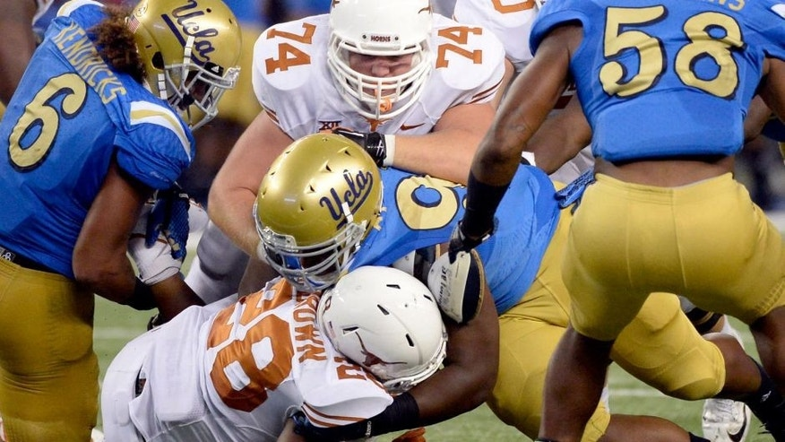Sep 13, 2014; Arlington, TX, USA; Texas Longhorns guard Taylor Doyle (74) and running back Malcolm Brown (28) tackle UCLA Bruins defensive lineman Kenny Clark (97) during the second half at AT&T Stadium. Mandatory Credit: Richard Mackson-USA TODAY Sports