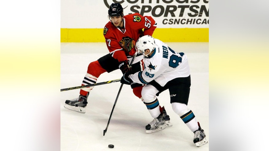 FILE - In this Dec. 20, 2015, file photo, Chicago Blackhawks defenseman Trevor van Riemsdyk, left, and San Jose Sharks left wing Matt Nieto battle for the puck during the first period of an NHL hockey game in Chicago. The emergence of the 24-year-old van Riemsdyk is a big reason why Chicago is once again among the top teams in the Western Conference at the NHL's Christmas break after a so-so start to the season. (AP Photo/Nam Y. Huh, File)