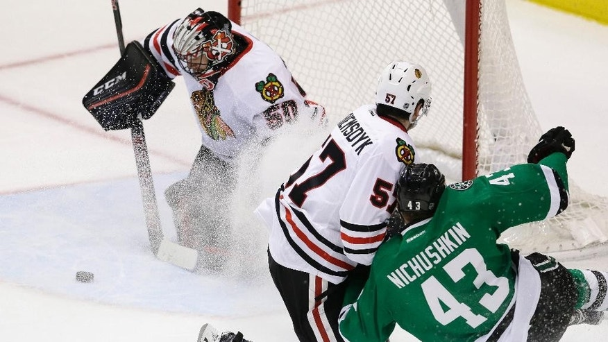 Chicago Blackhawks goalie Corey Crawford (50) and defenseman Trevor van Riemsdyk (57) defend the goal against Dallas Stars right wing Valeri Nichushkin (43) during the second period of an NHL hockey game Tuesday, Dec. 22, 2015, in Dallas. (AP Photo/LM Otero)