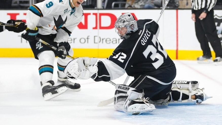 Los Angeles Kings goalie Jonathan Quick, right, makes a save in front of San Jose Sharks' Dainius Zubrus during the first period of an NHL hockey game Tuesday, Dec. 22, 2015, in Los Angeles. (AP Photo/Jae C. Hong)
