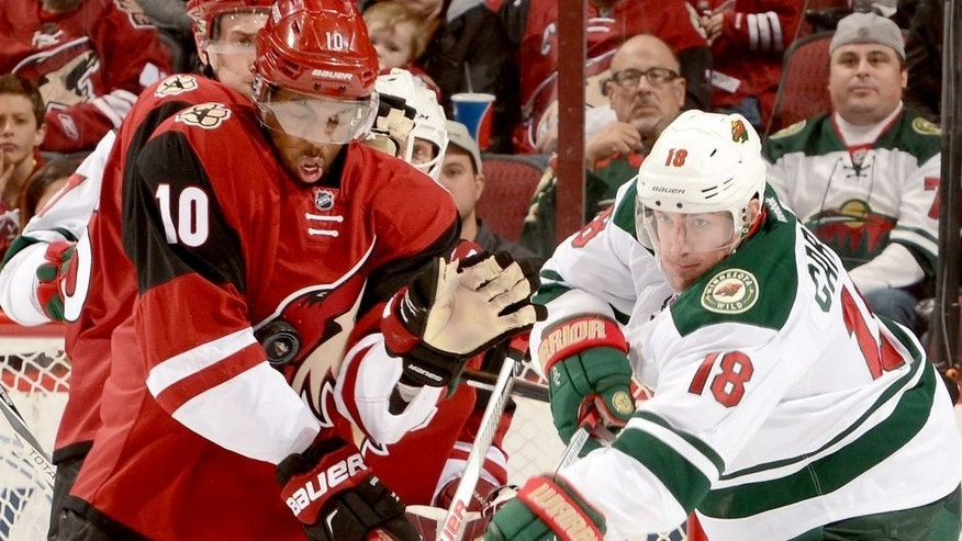 GLENDALE, AZ - DECEMBER 11: Anthony Duclair #10 of the Arizona Coyotes is hit in the chest with the puck as Ryan Carter #18 of the Minnesota Wild looks for a rebound at Gila River Arena on December 11, 2015 in Glendale, Arizona. (Photo by Norm Hall/NHLI via Getty Images)