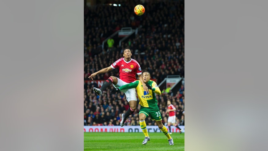 Manchester United's Anthony Martial, left, fights for the ball against Martin Olsson of Norwich City during the English Premier League soccer match between Manchester United and Norwich City at Old Trafford Stadium, Manchester, England, Saturday, Dec. 19, 2015. (AP Photo/Jon Super)