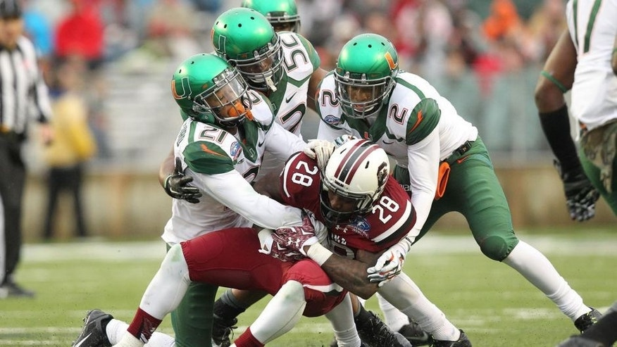 Dec 27, 2014; Shreveport, LA, USA; South Carolina Gamecocks tailback Mike Davis (28) is tackled during the first half as Miami Hurricanes linebacker Denzel Perryman (52) and defensive backs Deon Bush (2) and Antonio Crawford (21) make a tackle in the 2014 Independence Bowl at Independence Stadium. Mandatory Credit: Nelson Chenault-USA TODAY Sports