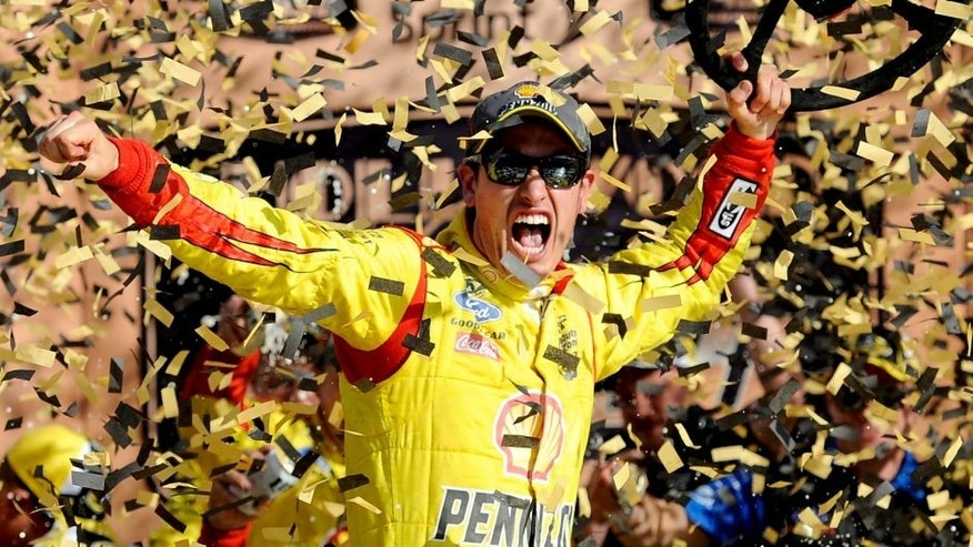 KANSAS CITY, KS - OCTOBER 05: Joey Logano, driver of the #22 Shell-Pennzoil Ford, celebrates in Victory Lane after winning the NASCAR Sprint Cup Series Hollywood Casino 400 at Kansas Speedway on October 5, 2014 in Kansas City, Kansas. (Photo by Jared C. Tilton/Getty Images)