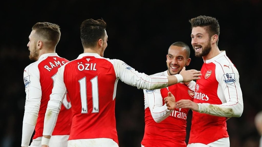 Arsenal's Theo Walcott, second right, is congratulated by teammates after scoring the opening goal of the game during the English Premier League soccer match between Arsenal and Manchester City at the Emirates stadium in London, Monday, Dec. 21, 2015. (AP Photo/Alastair Grant)