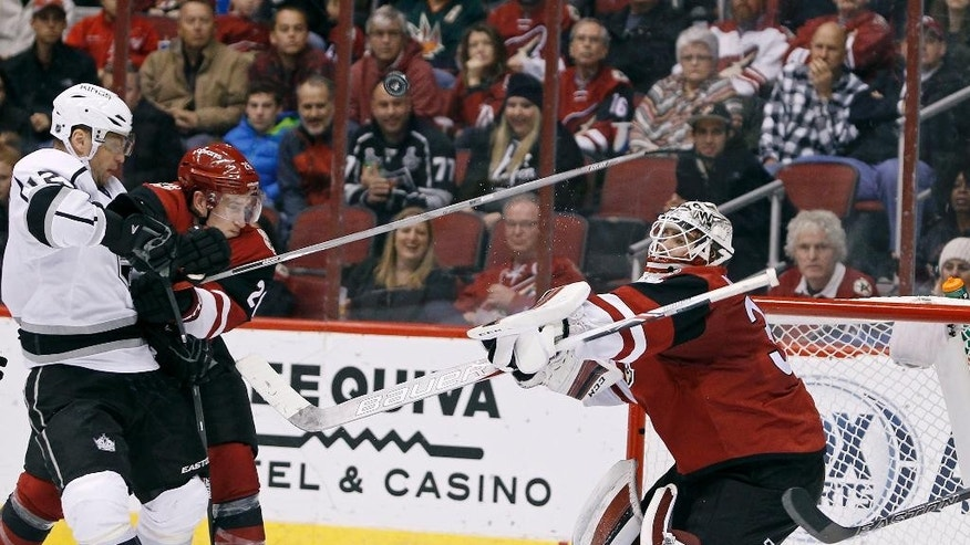 Arizona Coyotes goalie Louis Domingue, right, knocks the puck into the air on a blocker save as Los Angeles Kings' Marian Gaborik (12), of the Czech Republic, and Coyotes' Michael Stone look for a rebound during the second period of an NHL hockey game, Saturday, Dec. 26, 2015, in Glendale, Ariz. (AP Photo/Ralph Freso)