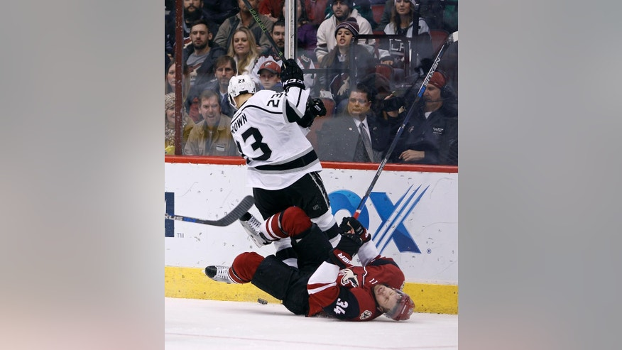 Arizona Coyotes' Klas Dahlbeck (34), of Sweden, falls to the ice as he collides with Los Angeles Kings' Dustin Brown during the second period of an NHL hockey game, Saturday, Dec. 26, 2015, in Glendale, Ariz. (AP Photo/Ralph Freso)