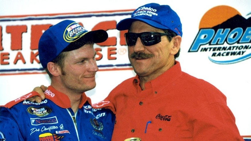 PHOENIX, AZ ? November 6, 1999: Although he finished second to Jeff Gordon in the Outback Steakhouse 200 at Phoenix International Raceway, Dale Earnhardt, Jr. (L) and his dad Dale Earnhardt (R) had plenty of reason to celebrate, as the younger Earnhardt clinched the NASCAR Busch Grand National Series championship even though there was still one race to run the following week at Homestead-Miami Speedway. (Photo by ISC Images & Archives via Getty Images)
