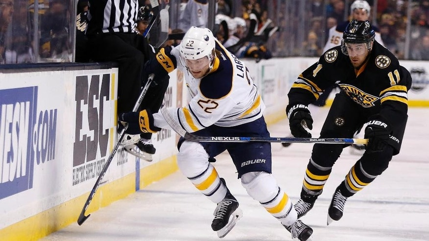 Buffalo Sabres' Johan Larsson (22) and Boston Bruins' Jimmy Hayes (11) battle for the puck during the first period of an NHL hockey game in Boston, Saturday, Dec. 26, 2015. (AP Photo/Michael Dwyer)