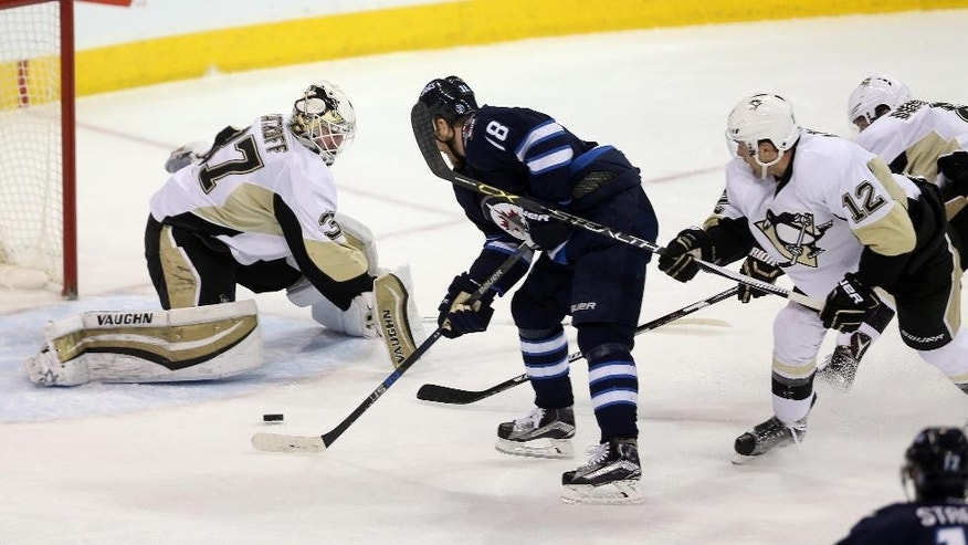 Winnipeg Jets' Bryan Little (18) is hooked on a breakaway by Pittsburgh Penguins' Ben Lovejoy (12) before shooting on goaltender Jeff Zatkoff (37) during the first period of an NHL hockey game in Winnipeg, Manitoba, Sunday, Dec. 27, 2015. (Trevor Hagan/The Canadian Press via AP) MANDATORY CREDIT