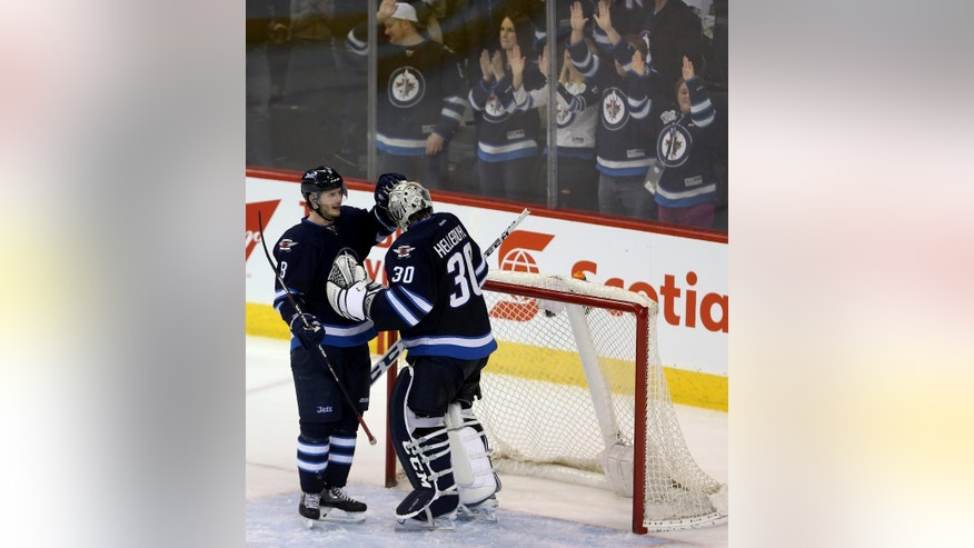 Winnipeg Jets' Jacob Trouba (8) congratulates goaltender Connor Hellebuyck (30) on his first career shutout in an NHL hockey game against the Pittsburgh Penguins in Winnipeg, Manitoba, Sunday, Dec. 27, 2015. The Jets won 1-0. (Trevor Hagan/The Canadian Press via AP) MANDATORY CREDIT