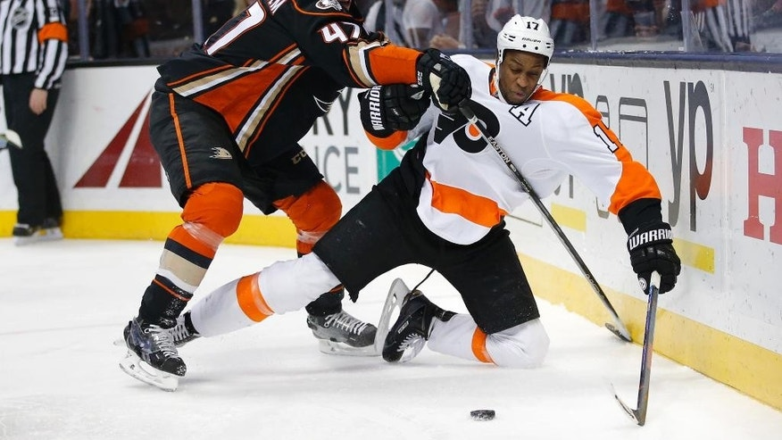 Philadelphia Flyers' Wayne Simmonds, right, and Anaheim Ducks' Hampus Lindholm, of Sweden, fight for the puck during the first period of an NHL hockey game, Sunday, Dec. 27, 2015, in Anaheim, Calif. (AP Photo/Jae C. Hong)