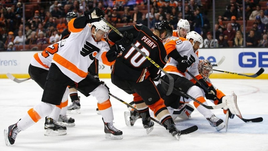 Anaheim Ducks' Corey Perry, center, shoots to score under pressure by Philadelphia Flyers' Chris VandeVelde, left, during the second period of an NHL hockey game, Sunday, Dec. 27, 2015, in Anaheim, Calif. (AP Photo/Jae C. Hong)