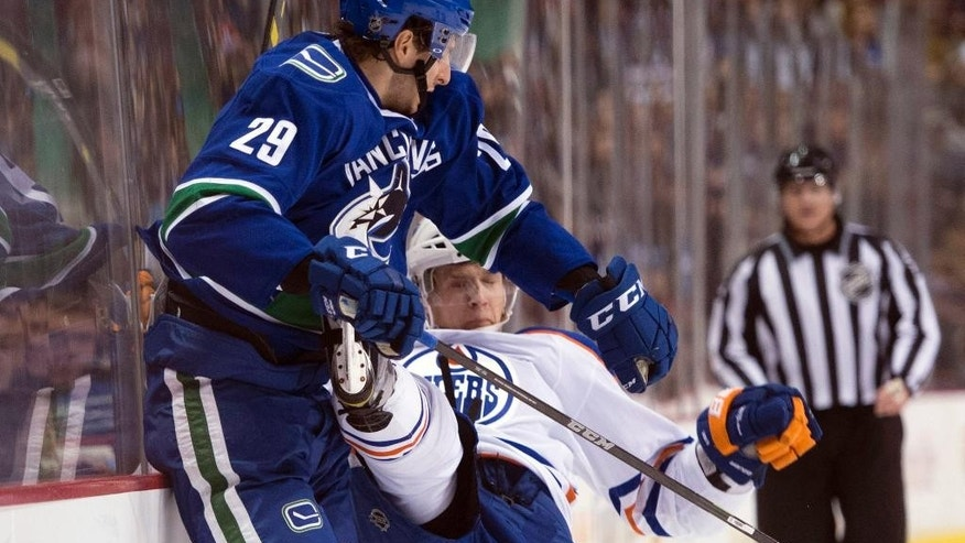 Vancouver Canucks defenseman Andrey Pedan (29) goes into the boards with Edmonton Oilers left wing Lauri Korpikoski (28) during first-period NHL hockey game action in Vancouver, British Columbia, Saturday, Dec. 26, 2015. (Jonathan Hayward/The Canadian Press via AP) MANDATORY CREDIT