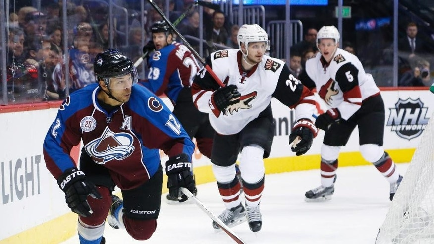 Colorado Avalanche right wing Jarome Iginla (12), left, looks to pass the puck as Arizona Coyotes defensemen Oliver Ekman-Larsson, center, of Sweden, and defenseman Connor Murphy defend in the first period of an NHL hockey game Sunday, Dec. 27, 2015, in Denver. (AP Photo/David Zalubowski)