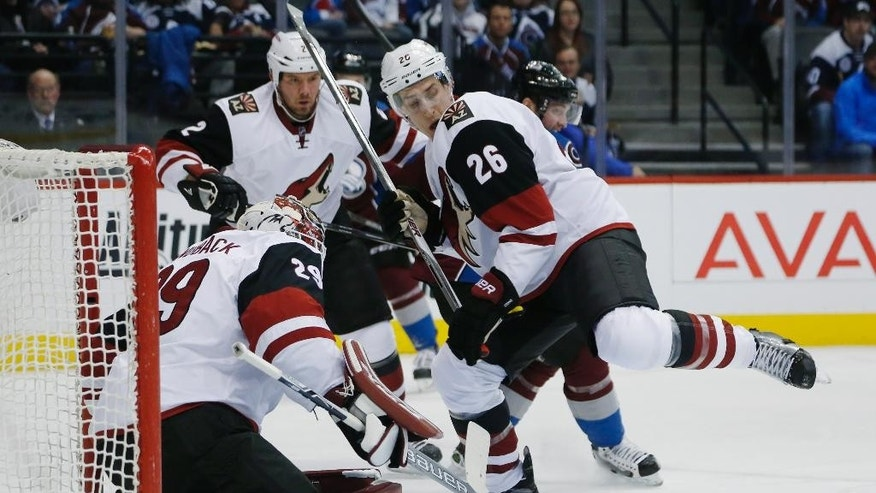 Arizona Coyotes goalie Anders Lindback (29), front, left, of Sweden, stops shot as defenseman Michael Stone, front right, pursues the puck while checking Colorado Avalanche center Matt Duchene, back, right, in the first period of an NHL hockey game Sunday, Dec. 27, 2015, in Denver. (AP Photo/David Zalubowski)