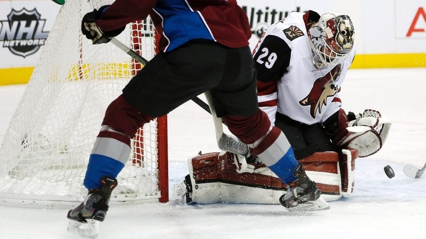 Arizona Coyotes goalie Anders Lindback, right, of Sweden, stops a shot off the stick of Colorado Avalanche right wing Jack Skille in the first period of an NHL hockey game Sunday, Dec. 27, 2015, in Denver. (AP Photo/David Zalubowski)