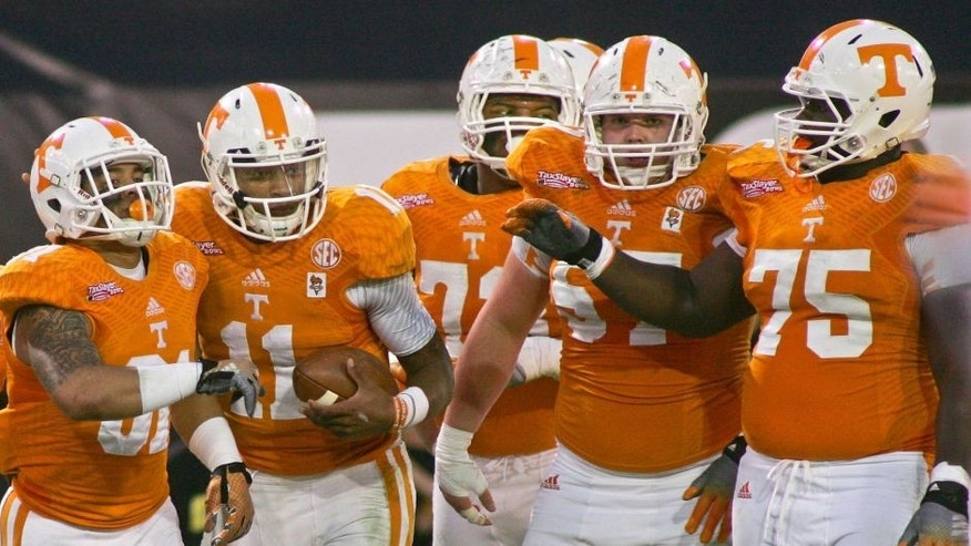 Jan 2, 2015; Jacksonville, FL, USA; Tennessee Volunteers quarterback Joshua Dobbs (second from left) is congratulated by wide receiver Johnathon Johnson (81) and guard Jashon Robertson (73) and center Mack Crowder (57) and offensive lineman Marcus Jackson (75) after scoring a touchdown in the third quarter of the 2015 TaxSlayer Bowl against the Iowa Hawkeyes at EverBank Field. The Tennessee Volunteers beat the Iowa Hawkeyes 45-28. Mandatory Credit: Phil Sears-USA TODAY Sports