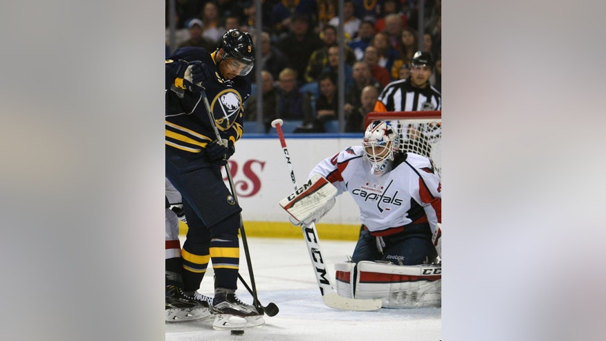 Buffalo Sabres left winger Evander Kane, left, has the puck deflect off his skate in front of Washington Capitals goaltender Braden Holtby, right, during the first period of an NHL hockey game, Monday Dec. 28, 2015 in Buffalo, N.Y. (AP Photo/Gary Wiepert)
