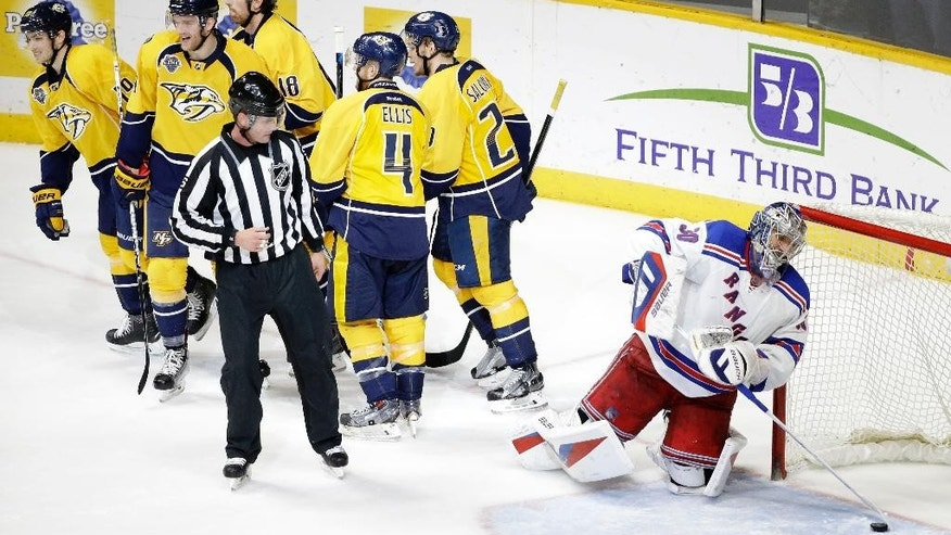 New York Rangers goalie Henrik Lundqvist (30), of Sweden, pulls the puck out of the net as Nashville Predators players head to the bench after a goal by Predators left wing James Neal (18) in the third period of an NHL hockey game Monday, Dec. 28, 2015, in Nashville, Tenn. (AP Photo/Mark Humphrey)