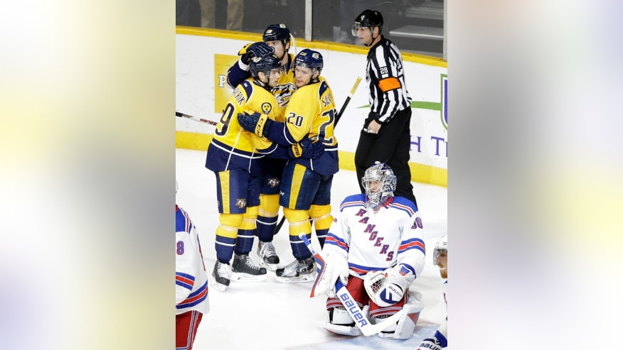 New York Rangers goalie Henrik Lundqvist (30), of Sweden, kneels on the ice as Nashville Predators Filip Forsberg (9), of Sweden; Miikka Salomaki (20), of Finland; and James Neal (18) celebrate a goal by Neal in the third period of an NHL hockey game Monday, Dec. 28, 2015, in Nashville, Tenn. (AP Photo/Mark Humphrey)