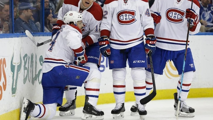 Montreal Canadiens center Tomas Plekanec (14), of the Czech Republic, is helped to his feet by teammates left wing Tomas Fleischmann (15), of the Czech Republic; right wing Sven Andrighetto (42), of Switzerland; and defenseman Nathan Beaulieu (28) after Plekanec scored against the Tampa Bay Lightning during the first period of an NHL hockey game Monday, Dec. 28, 2015, in Tampa, Fla. (AP Photo/Chris O'Meara)