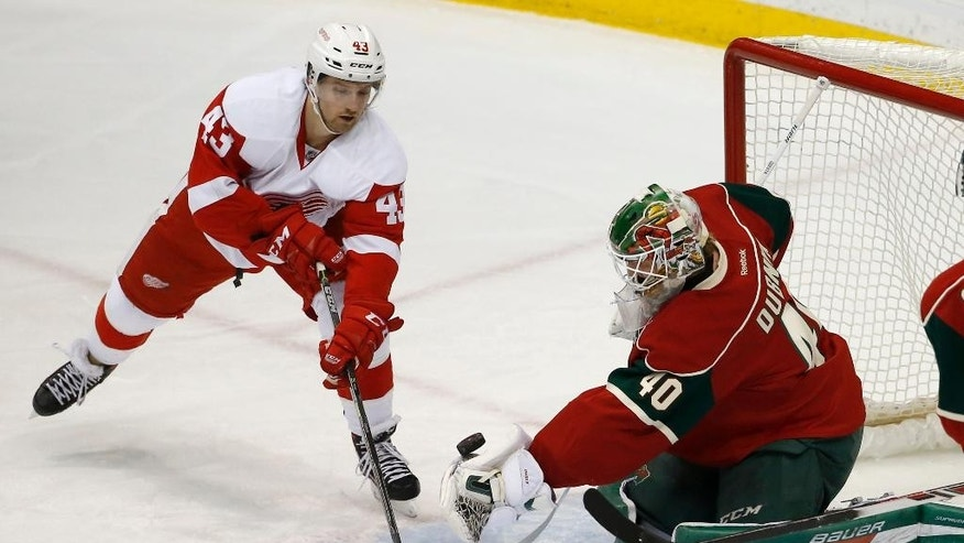 Minnesota Wild goalie Devan Dubnyk (40) scoops up a shot by Detroit Red Wings center Darren Helm (43) during the first period of an NHL hockey game in St. Paul, Minn., Monday, Dec. 28, 2015. (AP Photo/Ann Heisenfelt)