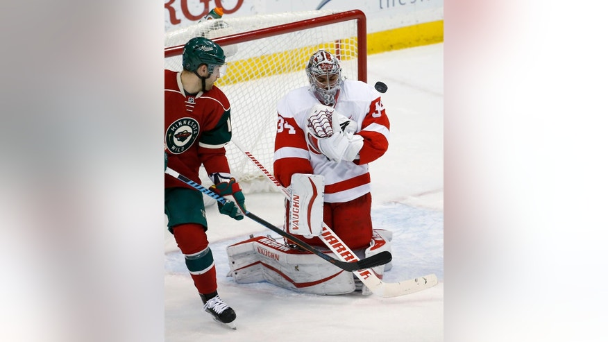 Detroit Red Wings goalie Petr Mrazek (34), of the Czech Republic, deflects a shot in front of Minnesota Wild left wing Jason Zucker during the first period of an NHL hockey game in St. Paul, Minn., Monday, Dec. 28, 2015. (AP Photo/Ann Heisenfelt)