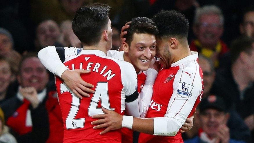 LONDON, ENGLAND - DECEMBER 28: Mesut Ozil (C) of Arsenal celebrates scoring his team's second goal with his team mates Alex Oxlade-Chamberlain (R) and Hector Bellerin (L) during the Barclays Premier League match between Arsenal and A.F.C. Bournemouth at Emirates Stadium on December 28, 2015 in London, England. (Photo by Ian Walton/Getty Images)