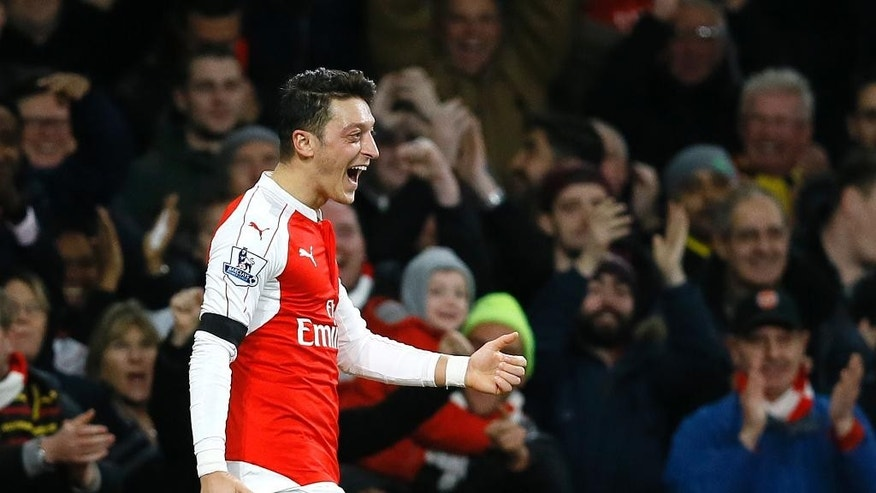 Arsenal's Mesut Ozil celebrates after scoring a goal,  during the English Premier League soccer match between Arsenal and Bournemouth at Emirates stadium in London, Monday, Dec. 28, 2015. (AP Photo/Kirsty Wigglesworth)