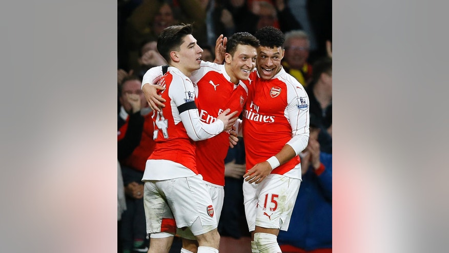 Arsenal's Mesut Ozil, centre, celebrates with Hector Bellerin, left, and Alex Oxlade-Chamberlain, right, after scoring a goal during the English Premier League soccer match between Arsenal and Bournemouth at Emirates stadium in London, Monday, Dec. 28, 2015. (AP Photo/Kirsty Wigglesworth)