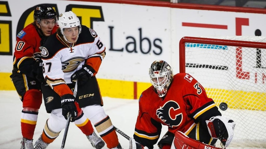 Anaheim Ducks' Rickard Rakell, center, watches as his shot go past Calgary Flames' goalie Karri Ramo, right, as Markus Granlund, looks on during the third period of an NHL hockey game in Calgary, Alberta, Tuesday, Dec. 29, 2015. (Jeff McIntosh/The Canadian Press via AP) MANDATORY CREDIT
