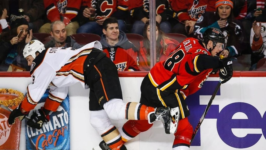 Anaheim Ducks' Chris Stewart, left, checks Calgary Flames' Matt Stajan during the first period of an NHL hockey game in Calgary, Alberta, Tuesday, Dec. 29, 2015. (Jeff McIntosh/The Canadian Press via AP) MANDATORY CREDIT