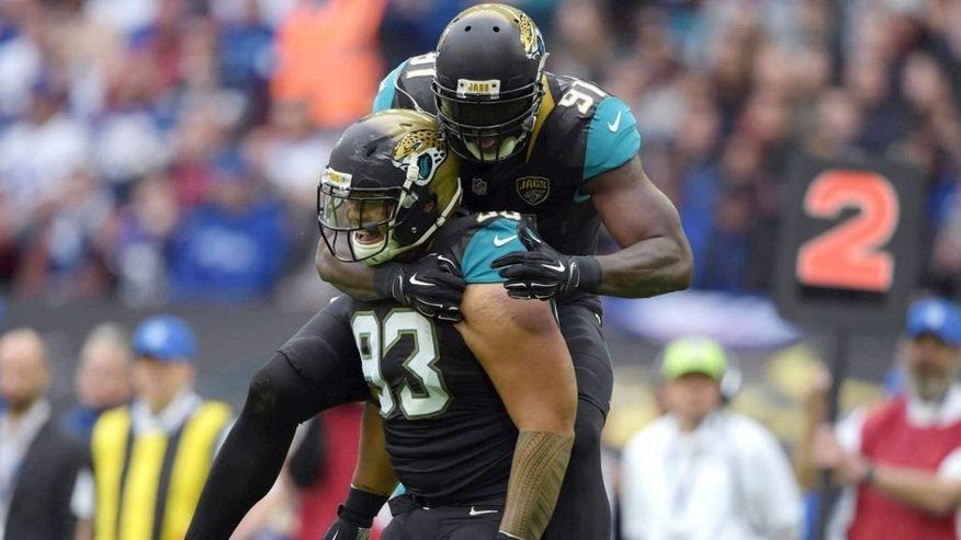 Oct 25, 2015; London, United Kingdom; Jacksonville Jaguars defensive end Tyson Alualu (93) celebrates with defensive end Chris Clemons (91) after a sack in the first quarter against the Buffalo Bills during NFL International Series game at Wembley Stadium. Mandatory Credit: Kirby Lee-USA TODAY Sports