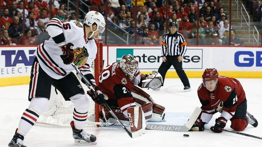 Chicago Blackhawks' Artem Anisimov, left, of Russia, has his shot stopped by Arizona Coyotes' Anders Lindback (29) and Michael Stone (26) during the first period of an NHL hockey game Tuesday, Dec. 29, 2015, in Glendale, Ariz. (AP Photo/Ross D. Franklin)